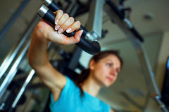 Athletic woman works out on training apparatus in gym. Athletic woman works out on training apparatus in fitness center Royalty Free Stock Photos