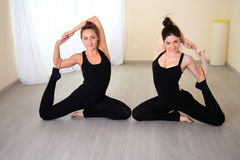 Athletic women dressed in beautiful sportswear doing yoga pose. Sitting on the floor. Training in the lit gym royalty free stock image