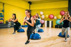 Athletic women group exercising, fitness training. Athletic women group in sportswear exercising on fitness training. Female sport teamwork in gym. Girs doing Royalty Free Stock Image