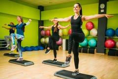 Athletic women on step aerobic training indoor Stock Photos