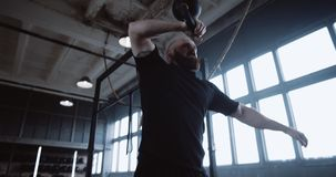 Athletic young bearded Caucasian man during extreme functional workout lifting kettlebell in large gym slow motion. Strength and motivation for success stock footage