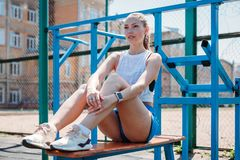 Athletic young beautiful blonde woman after sports training resting on sports ground stock photo