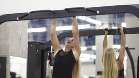 Athletic young blond female training on horizontal bar in black sportswear in gym performing pulls-up. Determined female bodybuilfer. Fitness and heathcare stock video