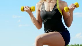Athletic young blond woman doing different exercises with weights, dumbbells, lunges, squats. Lake, river, blue sky and stock footage
