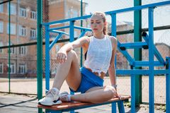 Athletic young blond woman sits and rests on sports field during her vacation from workouts. Athletic young blond woman sits and rests on the sports field during royalty free stock image