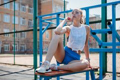Athletic young blond woman sits and rests on sports field during her vacation from workouts. Athletic young blond woman sits and rests on the sports field during stock images