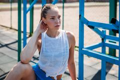 Athletic young blond woman sits and rests on sports field during her vacation from workouts. Athletic young blond woman sits and rests on the sports field during stock photos