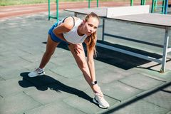 Athletic young blond woman on sports field does workout stock photos