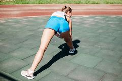 Athletic young blond woman on sports field does workout royalty free stock photos