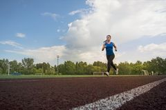 Athletic young sportswoman sprinting on running track stadium. Stock Images