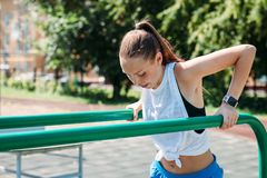 Athletic young blonde woman on gym outdoors doing workouts on bar royalty free stock images