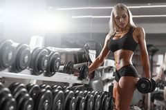Athletic young blondy doing exercise in the gym. Athletic young woman resting during exercise in the gym Stock Photos