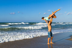 Athletic young couple does fitness exercises at the beach. Stock Image
