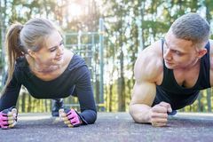 Athletic young couple doing exercise plank outdoors royalty free stock images