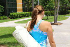 Athletic young female carrying a mat Royalty Free Stock Images