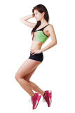 Athletic young girl in T-shirt and short shorts performs an exercise. Stock Image