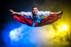 Athletic young handsome man in the Ukrainian national costume dance and jump on a dark background with smoke Stock Image