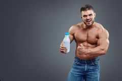 Athletic young handsome man with white shake bottle. Royalty Free Stock Photo