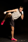 Athletic young kickboxer kicking during a fight Royalty Free Stock Images