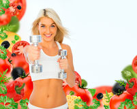 Athletic young lady doing workout with weights on white and vege. Tables Stock Images