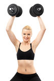 Athletic young lady working out with weights Stock Photography