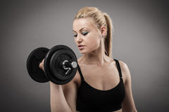 Athletic young lady working out with weights Stock Images