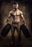 Athletic young man with car tire. Attractive athletic young man with two car tire Royalty Free Stock Images