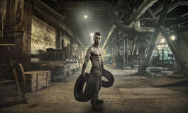 Athletic young man with car tire. Attractive athletic young man with two car tire in the workshop Stock Images