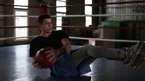Athletic young man doing abdomen exercise on the floor on the boxing ring. Man doing workout using a medicine ball at. The boxing gym stock video footage