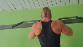 Athletic young man doing chin-ups at gym