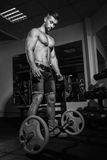 Athletic young man doing exercises with barbell in gym. Handsome muscular bodybuilder guy is working out. Monochrome image. Stock Images