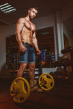 Athletic young man doing exercises with barbell in gym. Handsome muscular bodybuilder guy is working out. Vintage toning. Royalty Free Stock Images