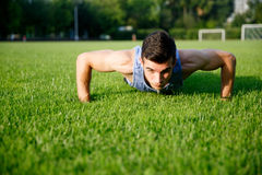 Athletic young man doing push-ups on green grass. On summer warm day stock photos