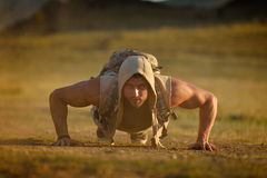 Athletic young man exercising outdoor on dusty field Royalty Free Stock Photo