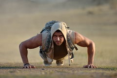 Athletic young man exercising outdoor on dusty field Royalty Free Stock Photos