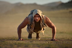 Athletic young man exercising outdoor on dusty field. In summer Royalty Free Stock Images