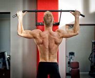 Athletic young man hanging from gym equipment. Blond, attractive young man hanging from gym equipment, seen from the back Stock Photo