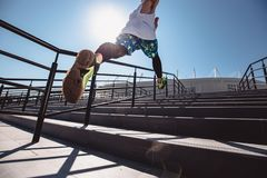 Athletic young man with headband on his head dressed in the white t-shirt, black leggings and blue shorts is jumping up royalty free stock photography