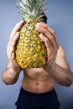 Athletic young man holding a fresh pineapple. On blue background Stock Images