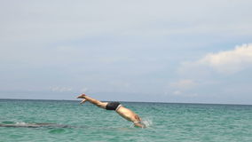 Athletic young man jumping from stone into ocean sea blue water. Muscular adventure sports lifestyle hobby vacation stock video footage