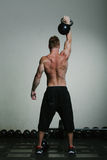 Athletic young man lifting weights Stock Photography