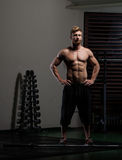 Athletic young man lifting weights Royalty Free Stock Images