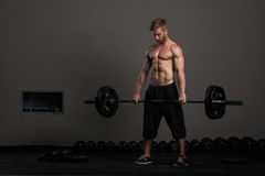 Athletic young man lifting weights Stock Photos