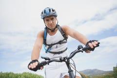 Athletic young man mountain biking Stock Photos