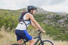 Athletic young man mountain biking Royalty Free Stock Photo