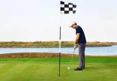 Athletic young man playing golf Stock Image