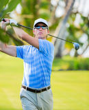 Athletic young man playing golf Stock Images