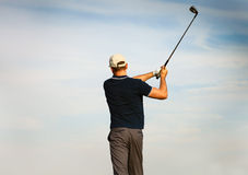 Athletic young man playing golf, golfer hitting fairway shot. Swinging club Royalty Free Stock Photo