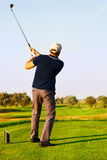 Athletic young man playing golf. Golfer hitting fairway shot, swinging club Stock Image