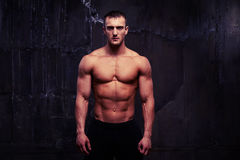 Athletic young man posing with bare torso against dark wall Royalty Free Stock Photography